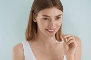 Dental care. Smiling woman using removable clean aligners