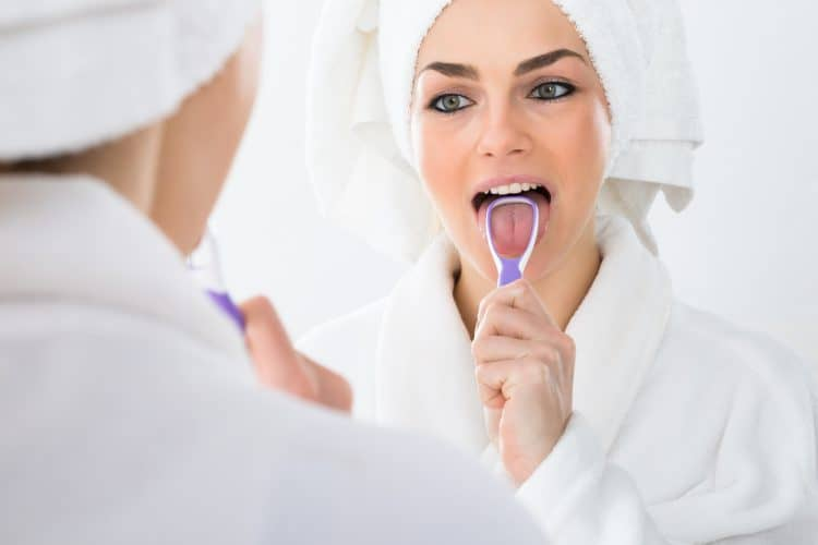 lady using tongue scraper to reduce bad breath