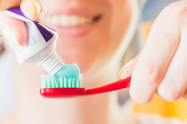 an image of a person brushing teeth with fluoride toothpaste